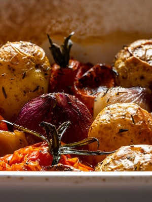 Roasted potatoes, vine ripe tomatoes and pearl onions in a ceramic roasting dish