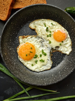 Tasty breakfast. Food on the table. Food on a dark concrete background. Fried eggs in a pan. Eggs, green onions, brown bread, cucumbers.