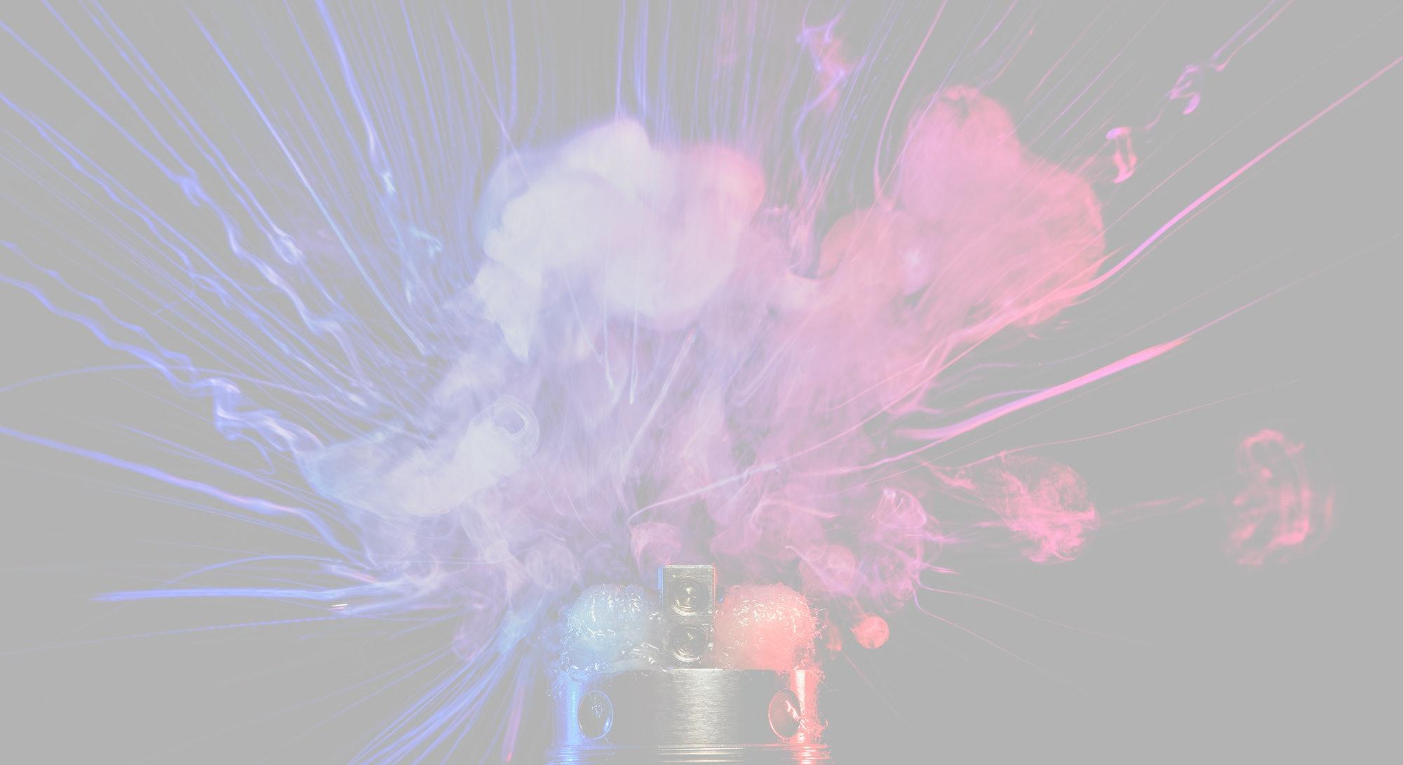 Electronic Cigarette vape explosion. Dark background.