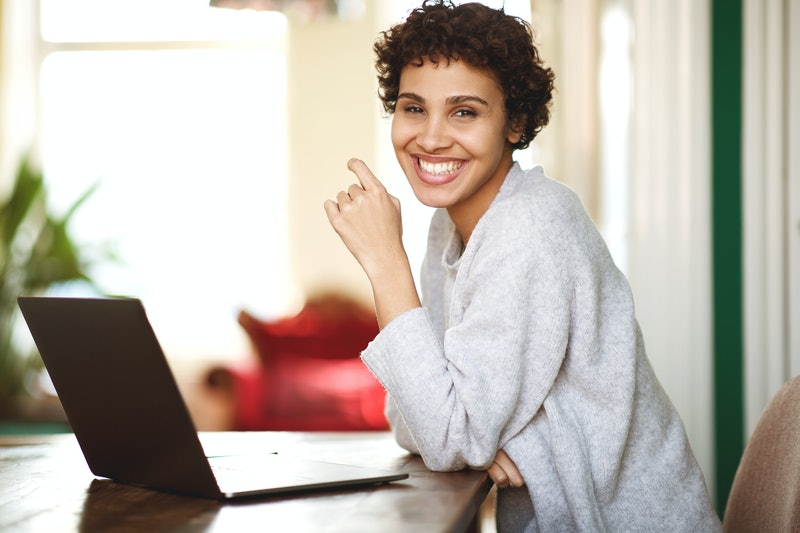 Portrait of happy african american woman with laptop computer at home