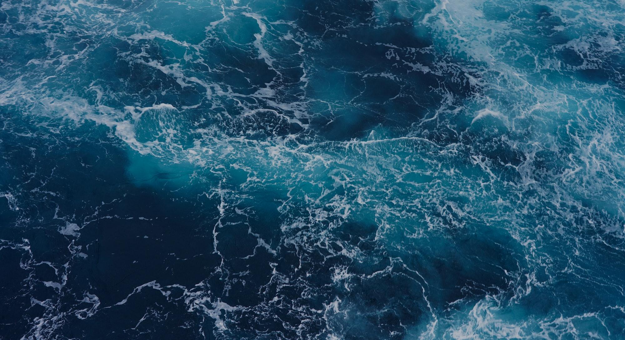 Abstraction of sea foam in the ocean. Dark water, storm waves