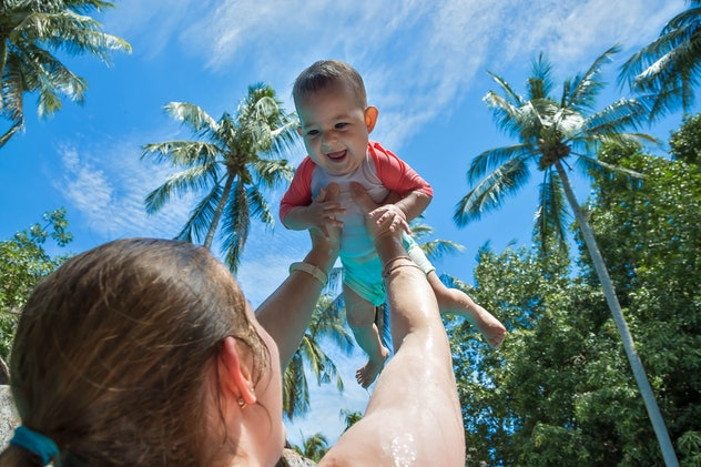 Mom raised baby high above the head in the pool. The little girl is very happy and screams for joy. ...