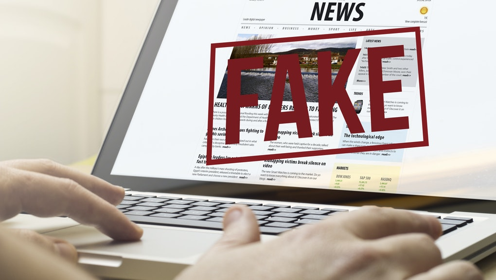 home computing concept: man using a laptop to read  fake news