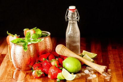 Strawberry Basil Moscow Mule cocktail in copper mugs on wooden table with strawberries, limes, Mudler,  simple syrup container and crushed ice.