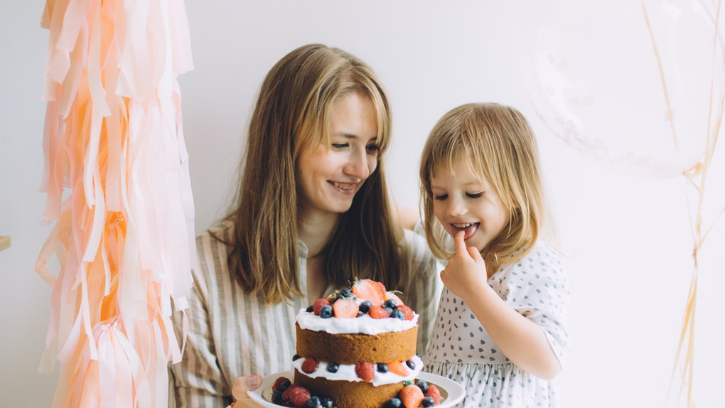 An aunt celebrates her niece's birthday with her with light pink decorations and a berry-covered cake.