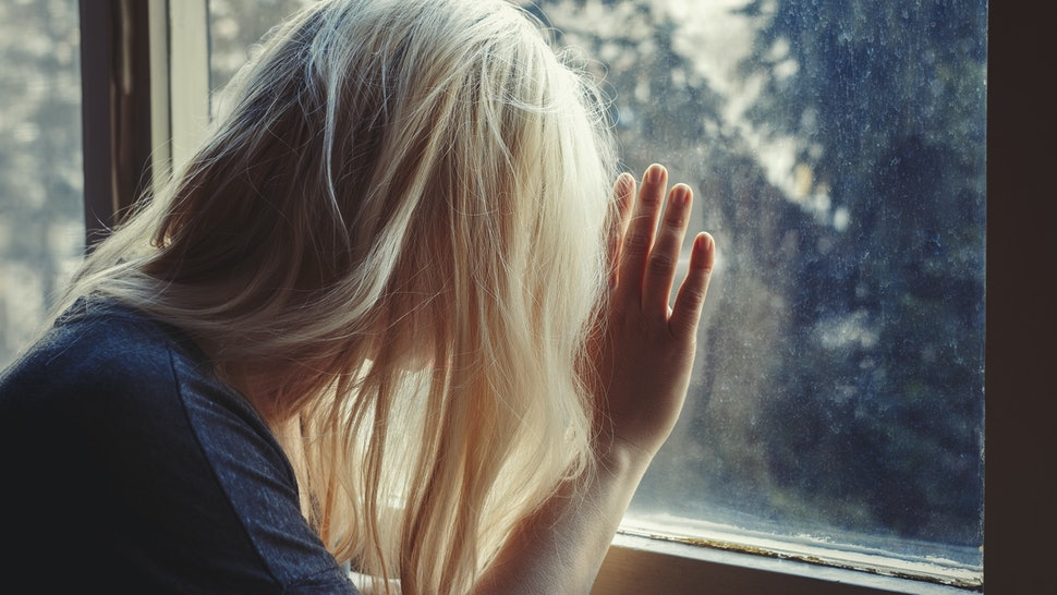 Blonde haired woman leaning against window, looking out, sad, depressed and lonely with unbrushed long hair, face not visible