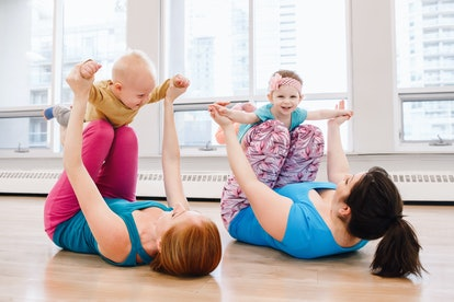 Group of two young women with children doing workout in gym class to loose baby weight. Child-friendly fitness for mothers with kids. Lifestyle concept of family activity for moms.