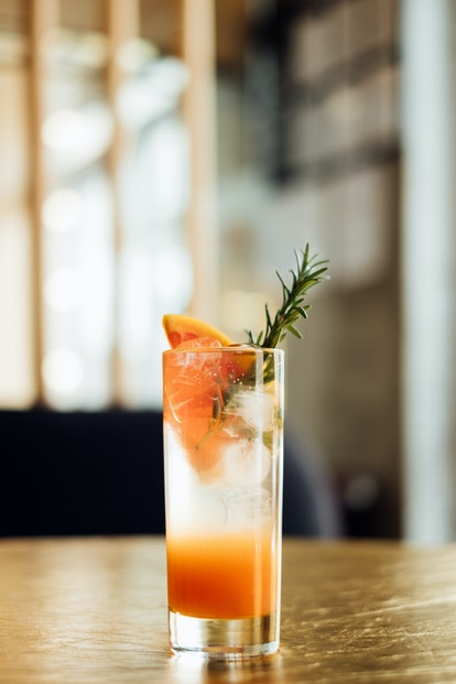 Paloma cocktail with fresh grapefruit on the wooden table, vertical composition
