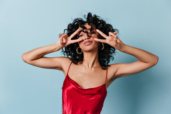 A woman wearing a red dress for Valentine's Day poses with two peace signs in front of her face.