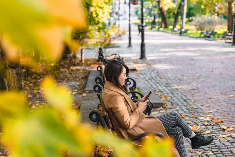 young adult fashion woman sitting at city park bench in autumn fall season sunny day