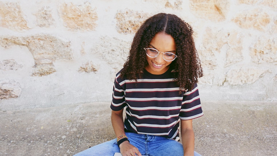 A portrait of happy smiling young black woman with curly hair wearing glasses, jeans and a striped t-shirt, sitting on the ground and working or making homework