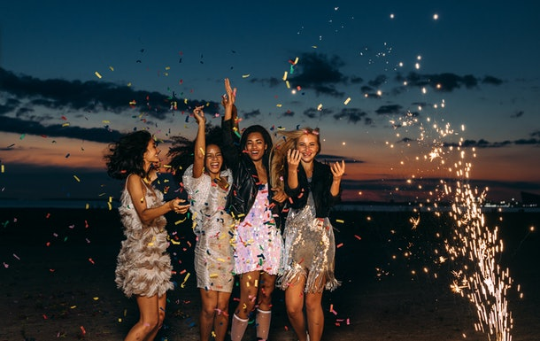 A group of friends celebrate a birthday on the beach with fireworks, confetti, and party dresses.