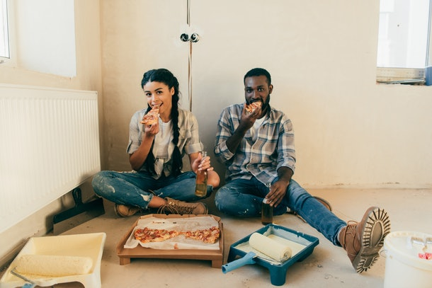 A couple enjoys their favorite pizza on the floor of their new apartment while it's being redone.