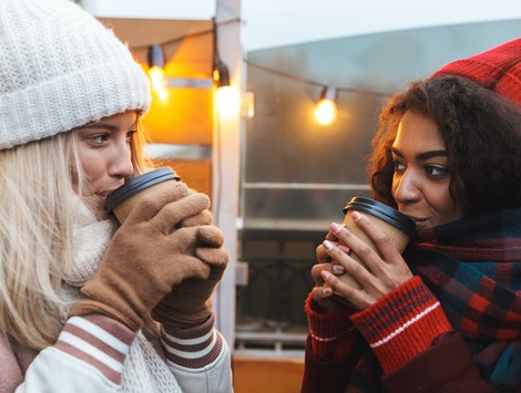 Image of a happy young friends girls talking with each other drinking coffee outdoors winter concept.