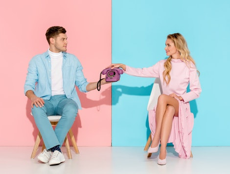 couple sitting on chairs and holding purple vintage telephone on pink and blue background