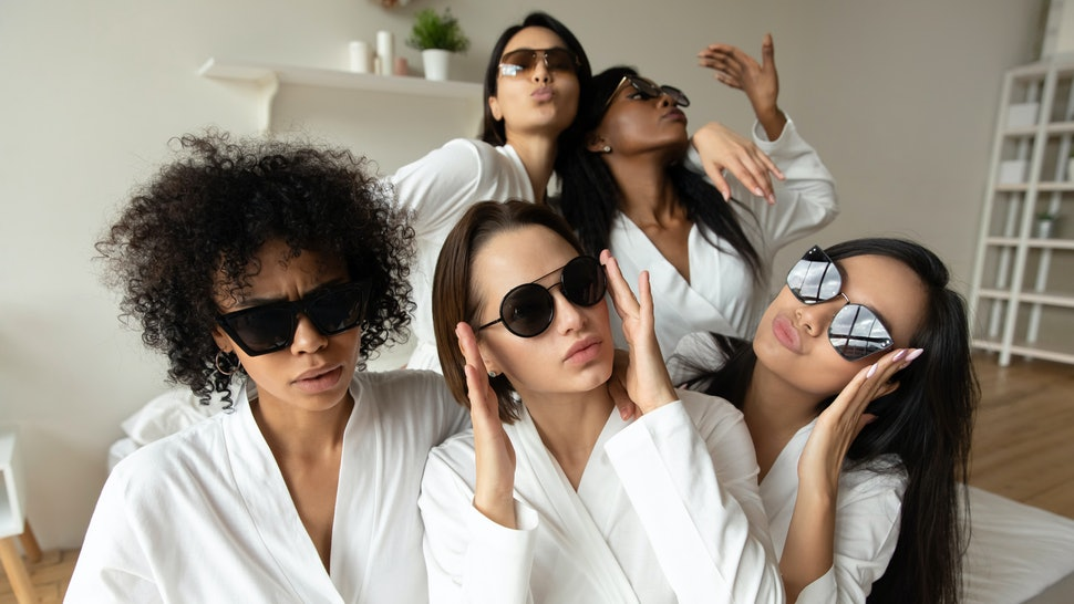 Funny cool young multiracial girls wear sunglasses bathrobes looking at camera, best friends ladies having fun together enjoy spa celebration bachelorette hen party in bedroom concept, group portrait