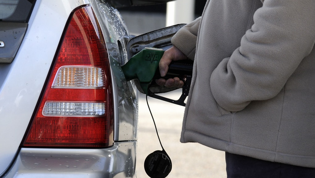 Man fills his car at a petrol pump