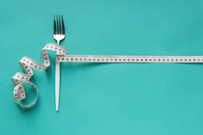 Fork and Measuring Tape on blue background, copy space. Diet, healthy lifestyle, weight loss concept...