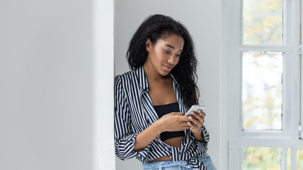 Cute Afro American pretty woman texting on mobile phone. Leisure time concept