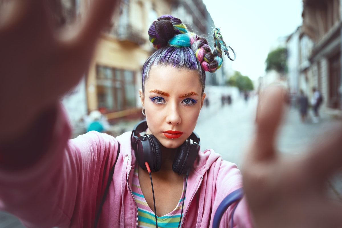 Cool funky young girl with headphones and crazy hair enjoy power of music taking selfie on street – ...