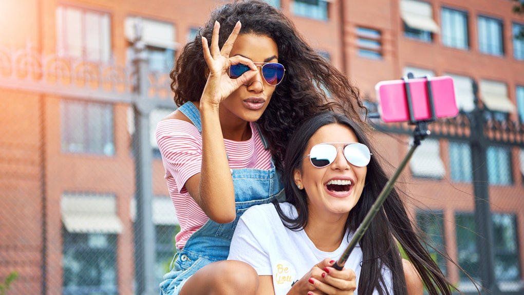 Two happy girls wearing cool sunglasses sit on a bench, laugh, and pose for a selfie on a summer day.