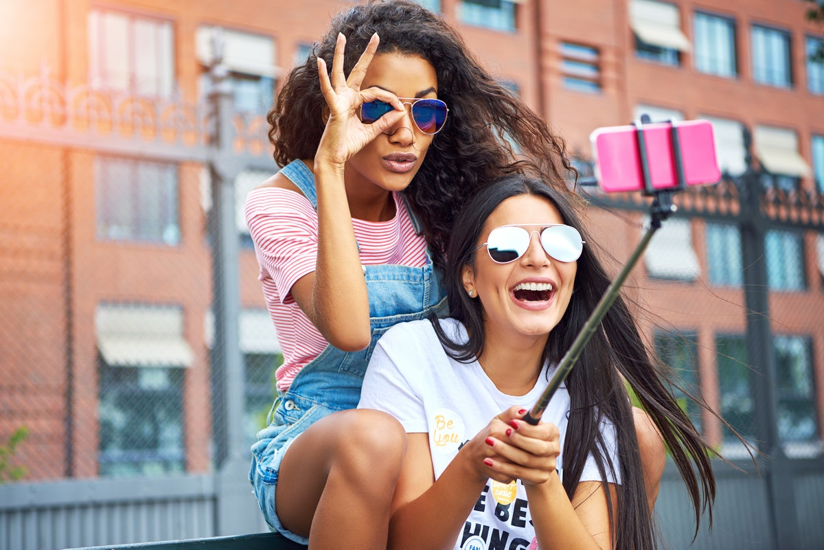 Two happy girls wearing cool sunglasses sit on a bench, laugh, and pose for a selfie on a summer day...
