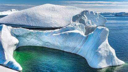 Antarctic iceberg and majestic landscape, sunny day, green lagoon