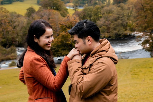Happy attractive Asian couple fall in love, man hold woman hand kiss with diamond ring after make proposal to get married engagement, young newlywed holiday, vacation honeymoon in Autumn season