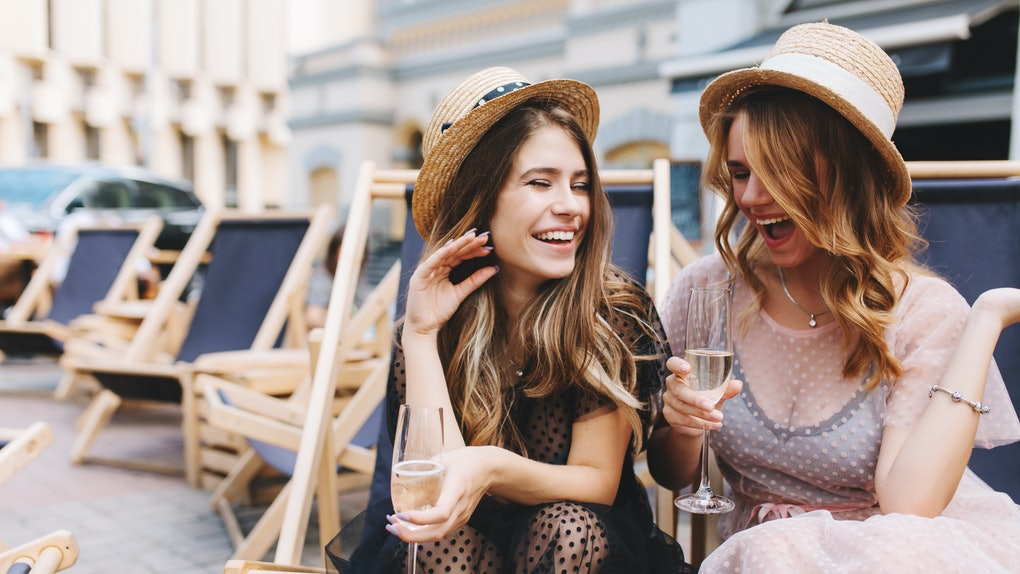 Two girls in dresses and hats laugh and hold their champagne glasses on a patio.