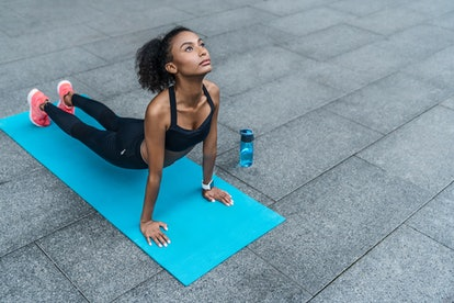 Young african sportswoman practising yoga outdoors