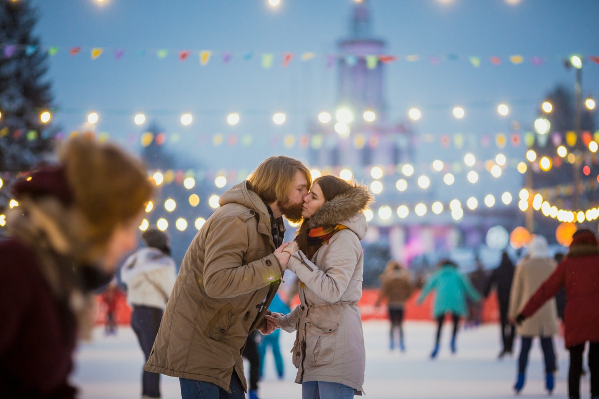 A young couple shares a kiss in the middle of an outdoor ice rink.