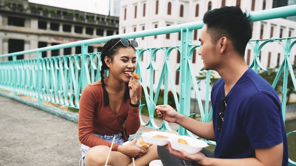 Young man feeding his girlfriend while they eating fast food on the ground in the city