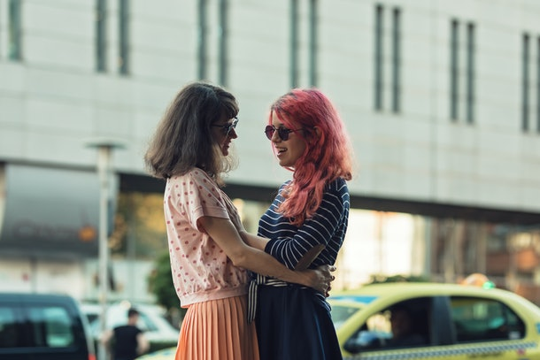 two lesbian girls, couple kiss romantically on the street in the city show love to each other gay pride LGBT pride world movement lesbian, gay, bisexual, transgender proud of their sexual orientation