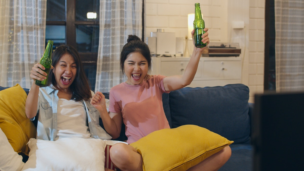 Two female friends cheer and raise their beer bottles on the couch while watching a game.