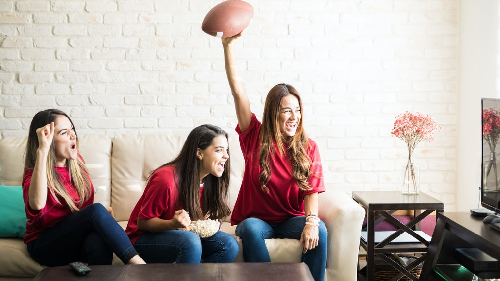 Three roomies wearing team jerseys and watching a football game on TV cheer on the couch.
