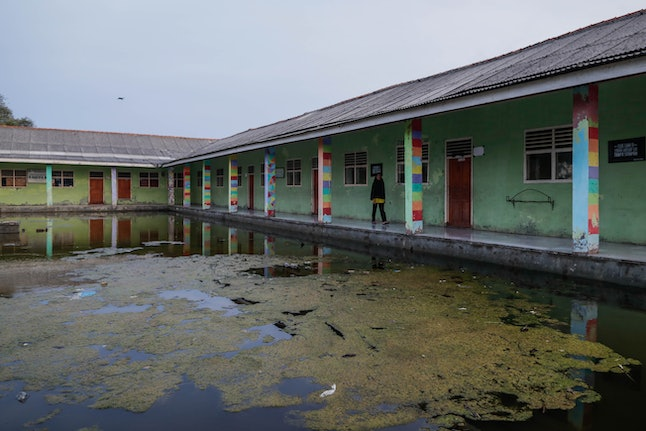 A villager walks along a flooded school yard at Pantai Bahagia village in Bekasi, West Java, Indonesia, 03 December 2019 (issued on 05 December 2019). Around 100 families living in Pantai Bahagia were forced to move as their houses were threatened by rising sea level. The village is one of the most affected by climate change in Indonesia.