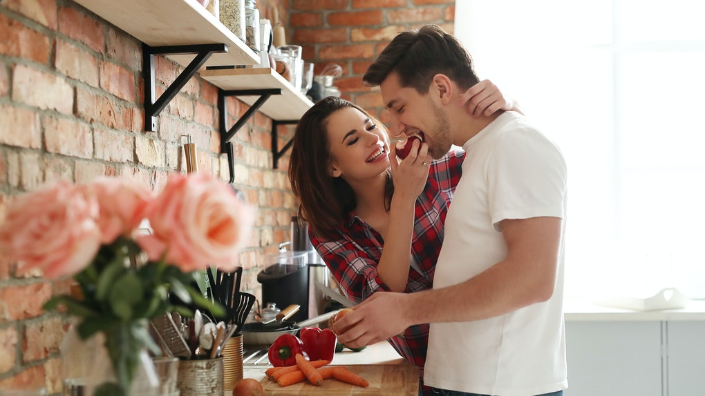 A happy couple prepares dinner in a bright kitchen on Valentine's Day.