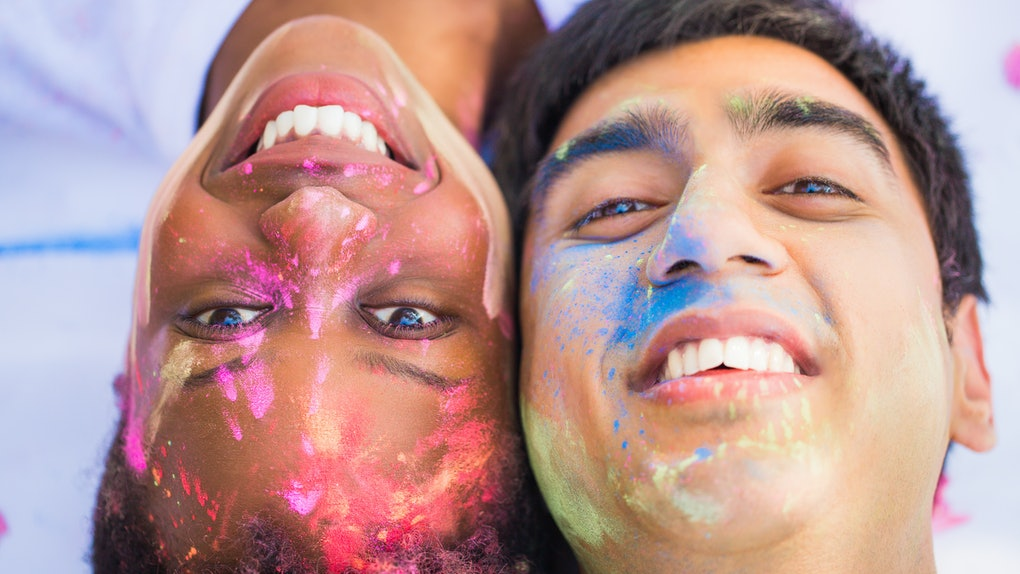 Close-up the young happy couple lying face to face with paints on their faces and smiling