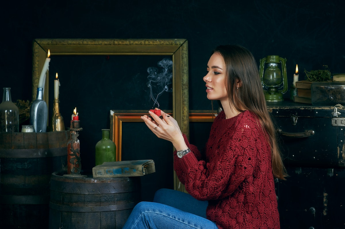 young woman with candles on dark background, divination and spiritualism