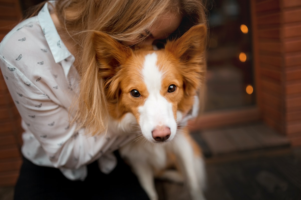 A woman cuddles with her border collie outside.