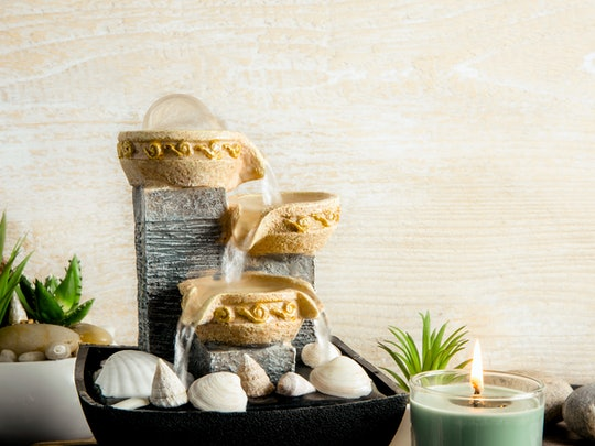 Portable indoor fountain for good Feng Shui in home or office. Small indoor tabletop fountain with water flowing. Spiritual mind and soul balance concept. Green plants in flower pot on background.