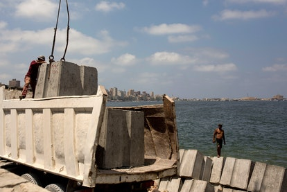 Workers prepare to place cement blocks to reinforce the sea wall against rising water levels on the ...