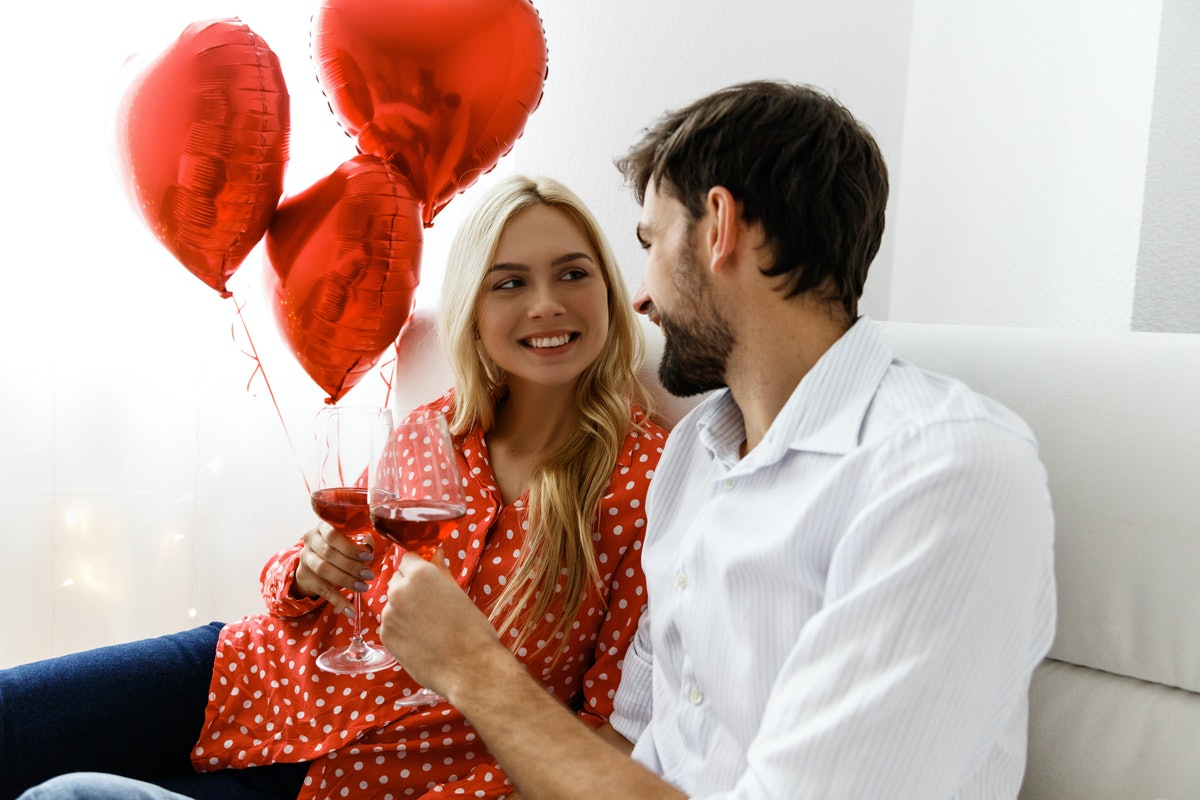 A woman and man clink their wine glasses while looking at each other on a couch on Valentine's Day.
