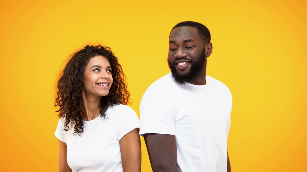 Happy couple flirting and smiling each other on yellow background, acquaintance