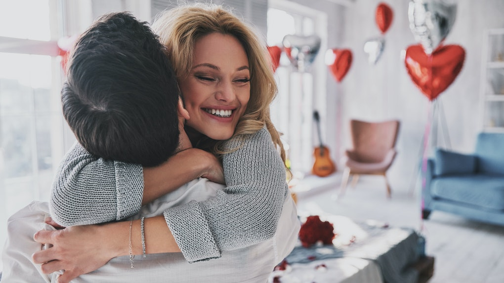 A happy blonde woman hugs her boyfriend who is lifting her up in the bedroom on Valentine's Day.