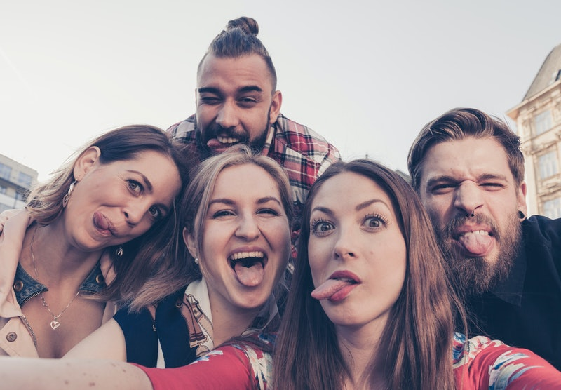 crazy best friends take a selfie downtown city environment poking out tongues making silly faces to share photograph on social media