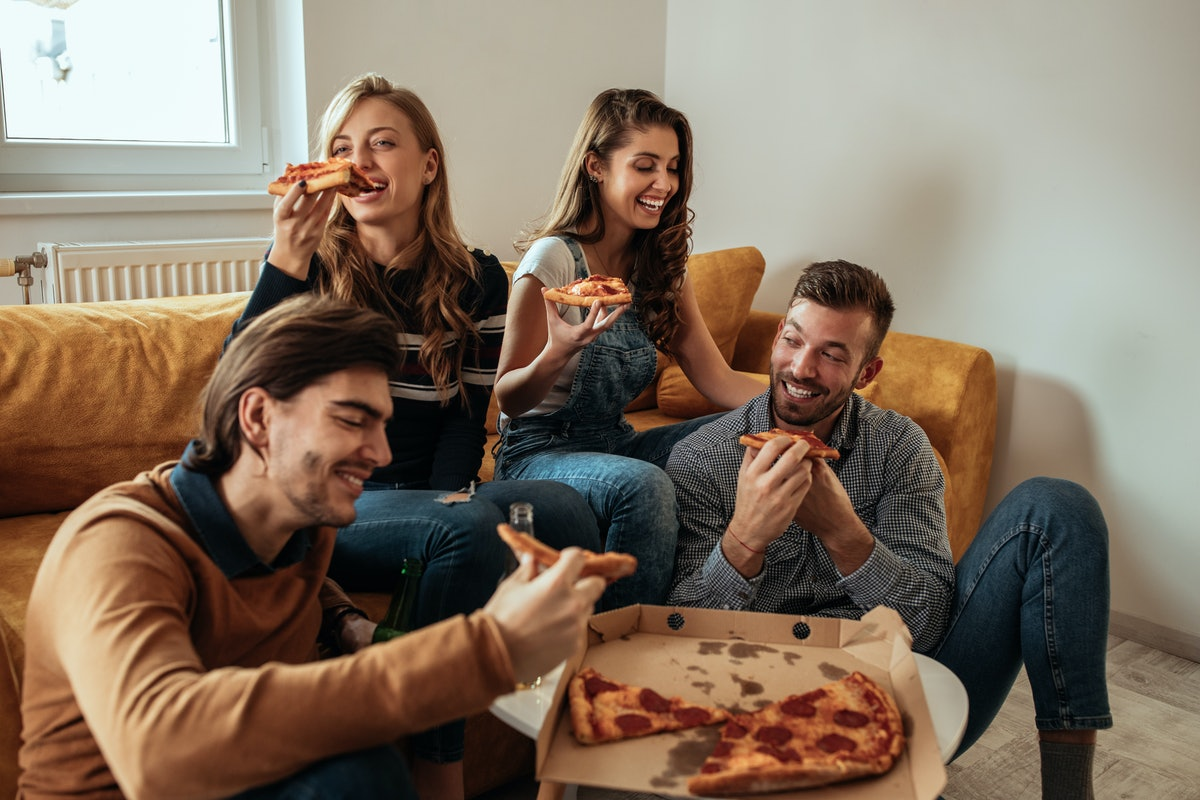 Two couples laugh and enjoy pizza in a bright living room.