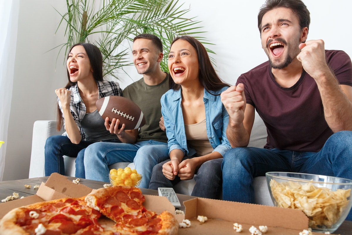 A group of four friends watch a football game on TV with a box of pizza and snacks in front of them.