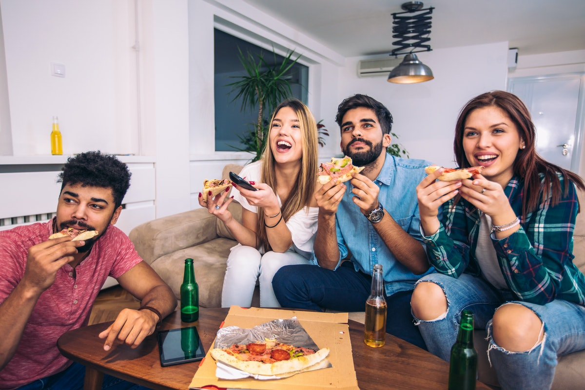A group of friends enjoy pizza on the couch while watching the football game on TV.