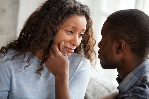 Loving African American man cheering beloved woman touching her face relaxing together at home, caring black boyfriend support mixed race girlfriend making her smile, looking in eyes